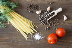 Noodles with spices. Herbs, garlic and tomatoes on a wooden desktop stock photo