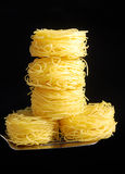 Noodles on spoon. Pasta in shape of nest on black background Stock Image