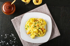 Noodles with swordfish, cream and saffron. On complex background Royalty Free Stock Photography