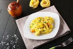 Noodles with swordfish, cream and saffron. On complex background Royalty Free Stock Images