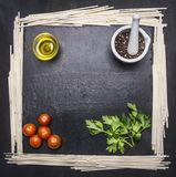 Noodles with tomatoes and oranges on  cutting board with herbs, frame space for text Stock Image