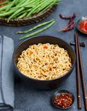 Noodles with vegetables in a bowl on grey stone background. royalty free stock image