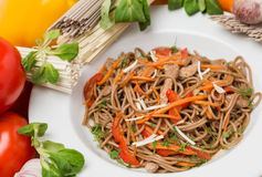 Noodles with vegetables and garnish on white plate Stock Image