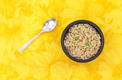 Noodles and vegetables with spoon in black bowl Stock Photo