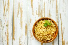 Noodles in Wooden bowl on Table and with green background. Royalty Free Stock Image