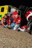 Noodsituatieteam die verwonde motorbestuurder helpen Royalty-vrije Stock Afbeeldingen