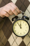Almost noon. Hand holding alarm-clock with 5 min before noon on it Royalty Free Stock Photo