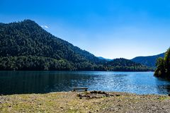 Noon on the mountain lake Ritsa. Midday landscape on the shore of lake Ritsa with views of the water and mountains stock photos