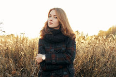 Noon portrait young beautiful redhead woman in scarf and plaid jacket on faded meadow cold season outdoors Royalty Free Stock Photos