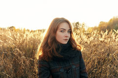 Noon portrait young beautiful redhead woman in scarf and plaid jacket on faded meadow cold season outdoors Stock Photo