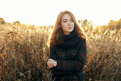 Noon portrait of young beautiful redhead woman in scarf and plaid jacket standing on faded meadow cold season outdoors Royalty Free Stock Images