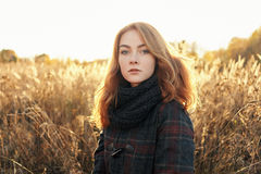 Noon portrait of young beautiful redhead woman in scarf and plaid jacket standing on faded meadow cold season outdoors Stock Photography