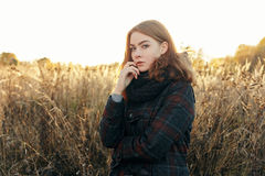 Noon portrait of young thoughtful redhead woman in scarf and plaid jacket standing on faded meadow cold season outdoors Royalty Free Stock Photo