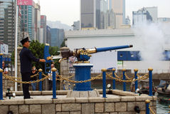 Noonday gun, Causeway Bay, Hongkong. An officer fires the Noonday Gun in Causeway Bay, Hongkong. The tradition seems to have originated over an incident in the Stock Image