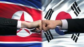 Noord-Korea versus het conflict van Zuid-Korea, vuisten tegen vlagachtergrond, diplomatie stock videobeelden