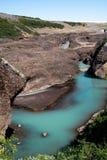 Noordelijke ijzige rivier die in een kleine canion stromen stock fotografie