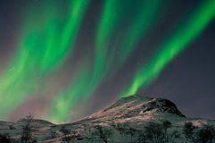 Noordelijke lichten boven bergbovenkant stock foto's