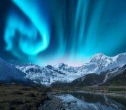 Noordelijke lichten boven sneeuw behandelde rotsen Het landschap van de winter royalty-vrije stock foto