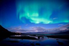 Noordelijke lichten die over kalm meeraurora borealis dansen stock foto's