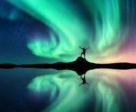 Noordelijke lichten en mens dichtbij meer met bezinning in water stock afbeelding