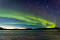 Noordelijke Lichten en ochtenddageraad over bevroren meer Stock Foto