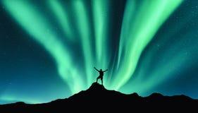 Noordelijke lichten en silhouet van de bevindende gelukkige mens aurora royalty-vrije stock foto