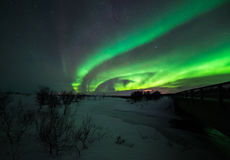 Noordelijke lichten met sneeuw en brug Stock Afbeelding