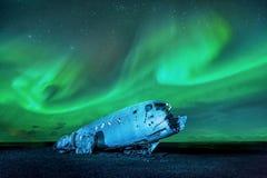 noordelijke lichten over vliegtuigwrak in IJsland stock afbeeldingen