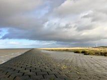 Noordzeekust in het Oosten Frisia Ostfriesland met Dramatische Wolken en Licht stock afbeeldingen