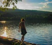 Noors meisje op de fjord bij zonsondergang Royalty-vrije Stock Foto's