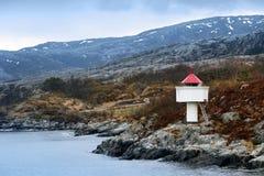 Noorse vuurtoren. Witte toren met rode bovenkant stock fotografie