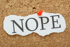 NOPE. The word Nope typed on a scrap of torn paper and pinned to a cork notice board. The word is a well known meme and modern slang for saying no or never Royalty Free Stock Image