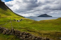 Norðradalur. A small village in the Faroe Islands. The island of Koltur in the background Royalty Free Stock Image