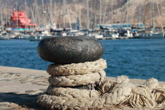 Noray with rope. Noray port with rope tied and at the back boats docked Royalty Free Stock Images