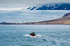 Nordenskioldbreen. A small boat is approaching the Nordenskiold Glacier. Isfjorden, Longyearbyen, Svalbard, Norway royalty free stock photos