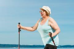 Nordic de pratique de femme supérieure marchant sur la plage photo libre de droits