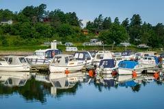 Nordic fishing boats moored at calm lake shore Stock Image