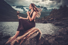 Nordic goddess in ritual garment with hawk near wild mountain lake in Innerdalen valley. Stock Photo