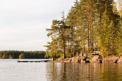 Nordic lake landscape of a wooden dock at a rocky shore with pine trees. In the evening sun Stock Images