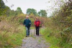 Nordic mayor de los pares que camina en el rastro en naturaleza Foto de archivo