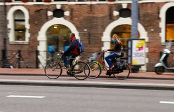 Nordic Outdoor Lifestyle, Focus Continuous Effect - Blonde Young Woman and Black Man Riding Bikes stock images
