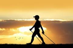 Nordic que camina en la puesta del sol Foto de archivo