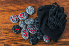 Nordic runes with velvet bag on rustic table Stock Images