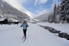 Nordic Skiing, Klosterle am Arlberg, Vorarlberg, Austria. Young woman cross-country skiing through Klosterle am Arlberg village in Tirol - Austria Stock Photos