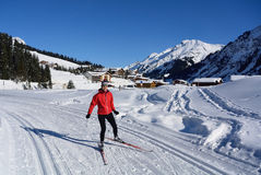 Nordic Skiing in Lech. Woman skiing on cross-country ski trail in village Lech in Voralberg - Austria Royalty Free Stock Image