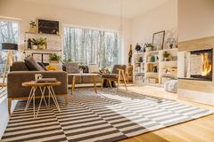 Nordic style living room interior with striped carpet, corner co. Uch with pillows, fireplace, big window and library on white rack stock photo