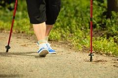 Nordic supérieur de femme active marchant en parc pattes Photographie stock libre de droits