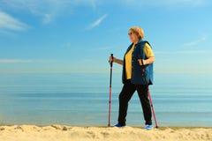 Nordic supérieur de femme active marchant sur une plage image stock