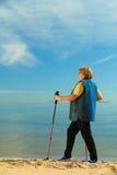 Nordic supérieur de femme active marchant sur une plage images stock