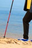 Nordic supérieur de femme active marchant sur une plage pattes Image libre de droits